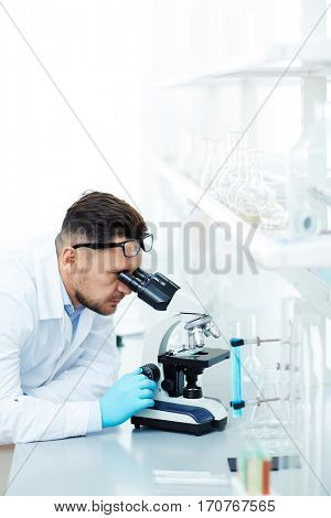Scientist or chemist looking in microscope in laboratory