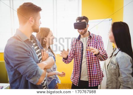 Business people looking at coworker wearing virtual reality headset in creative office
