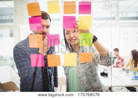 Creative business people looking at multi colored sticky notes on glass in meeting room at creative office