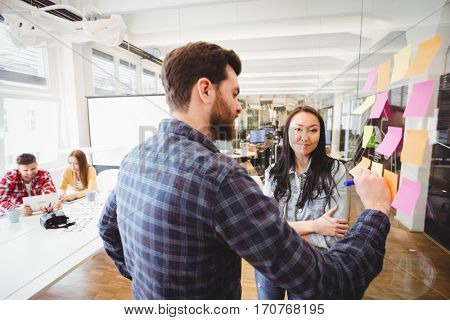 Portrait of female photo editor standing near male coworker writing on sticky note in meeting room