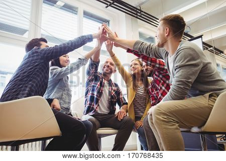 Low angle view of happy creative business people giving high-five in meeting room at creative office