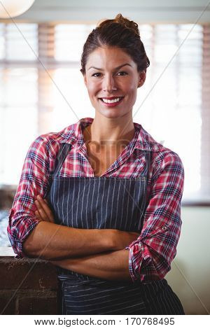 Waitress standing with arms crossed in a restaurant