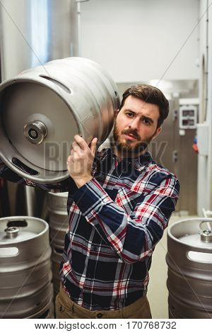 Portrait of manufacturer carrying keg in brewery