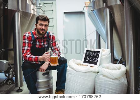 Portrait of manufacturer holding beer glass while sitting at brewery