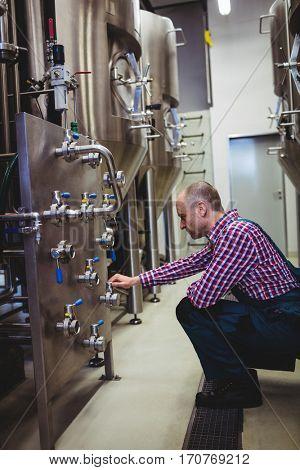 Mature manufacturer adjusting pressure gauge in brewery