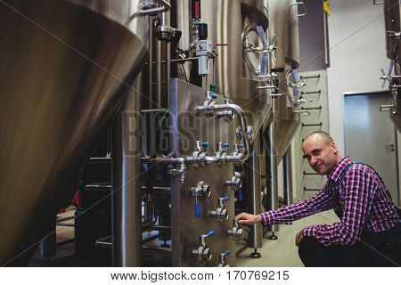 Manufacturer crouching while adjusting pressure gauge in brewery
