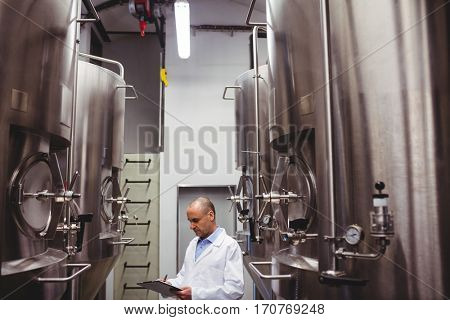 Manufacturer writing while standing amidst storage tanks at brewery