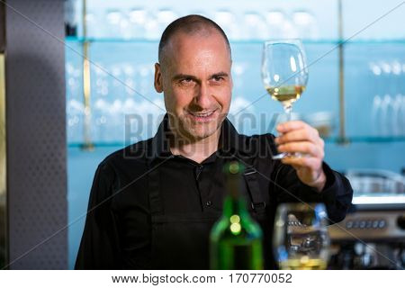 Waiter looking at a glass of wine in restaurant