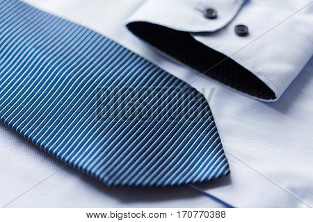 clothing, formal wear, fashion and objects concept - close up of shirt and patterned tie