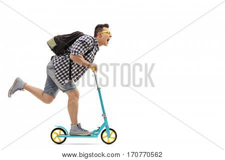 Full length profile shot of an overjoyed guy with a backpack riding a scooter isolated on white background