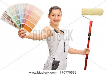 Happy female decorator with a color swatch and a paint roller isolated on white background