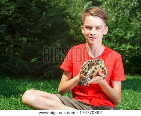 Cute teenager boy wearing red t-shirt sitting on a lawn in a summer garden holding turtle looking at camera smiling focus on turtle
