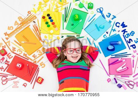 Little girl with school supplies books drawing and painting tools and materials. Happy back to school student. Art and crafts for kids. Child learning rainbow colors alphabet letters and numbers.