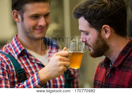 Brewers smelling beer at brewery factory