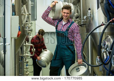 Portrait of brewers carrying keg at brewery factory