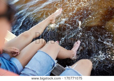 holidays, vacation, love and people concept - legs of young couple sitting on river berth