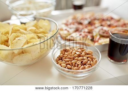 fast food and unhealthy eating concept - roasted peanuts, potato crisps and glass of cola drink on table