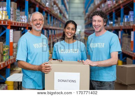 Happy volunteers are smiling and posing with a donations box in a warehouse