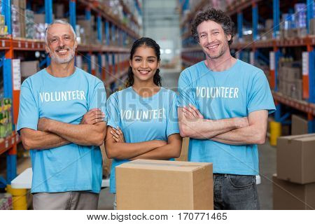 Happy volunteer are posing with crossed arms in a warehouse