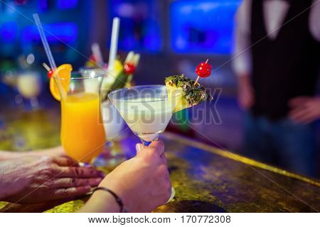 Cropped image of customers holding cocktail glasses by bartender at nightclub