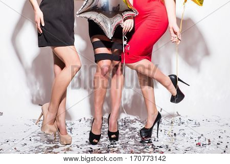 Closeup of legs of women standing on the floor with confetti and having party over white background