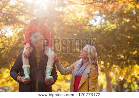 Father carrying daughter on shoulder while standing at park during autumn