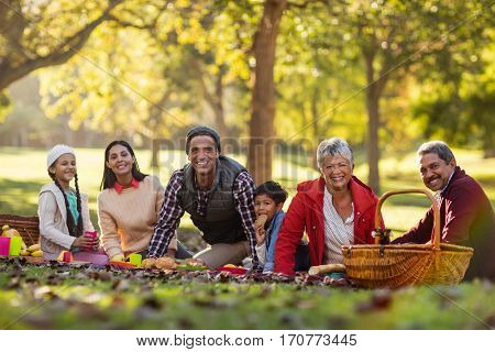 Portrait of joyful family relaxing against trees at park