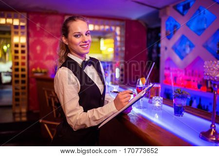 Portrait of young barmaid writing in clipboard at illuminated bar counter