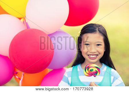 Portrait of smiling girl holding balloons and lollypop in the park on a sunny day