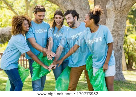 Group of volunteer forming hands stack while collecting rubbish in park