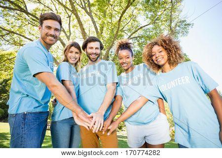 Portrait of volunteer group forming hands stack in park