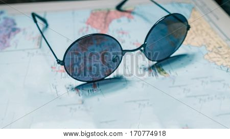 Round-eye sunglasses on the old paper map. Close-up. Wide angle