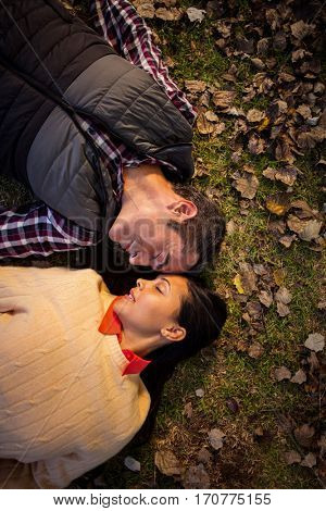 High angle view of couple romancing wihle lying on back at park