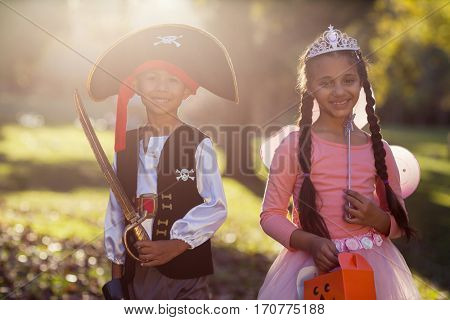 Portrait of happy siblings wearing costumes at park on sunny day
