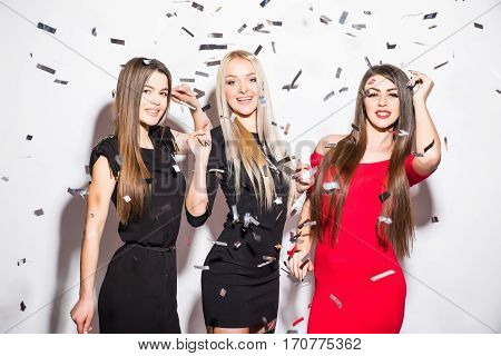 Pretty young women with star shaped balloons and confetti dancing and having party over white background