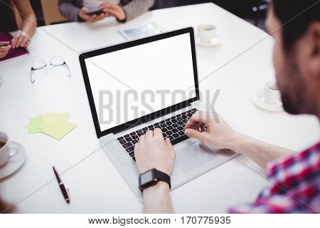 High angle view of young male executive using laptop in meeting room at creative office