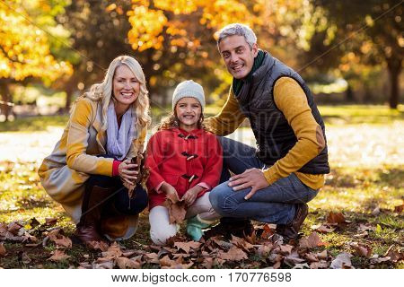 Portrait of happy family crouching at park during autumn