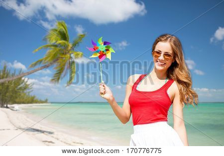 summer holidays, travel, people and vacation concept - happy young woman in sunglasses with pinwheel over exotic tropical beach with palm trees and sea shore background