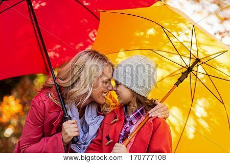 Cheerful mother and daughter rubbing noses while holding umbrella at park