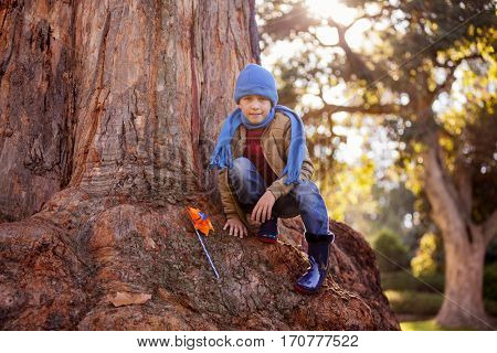 Portrait of boy with pinwheel while crouching on tree trunk at park