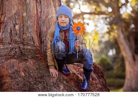 Portrait of cute aboy holding pinwheel while crouching on tree trunk at park