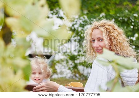 Happy woman and daugther in autumn at garden