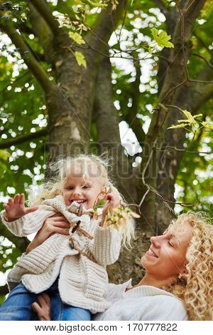 Mother and daugther happy together and playing in autumn