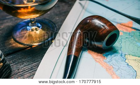 Brandy snifter and tobacco pipe on old map book. Close-up