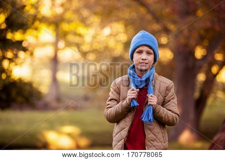Portrait of boy holding scarf while standing at aprk