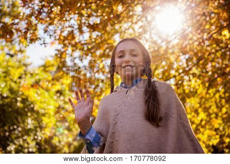 Low angle view of smiling girl waving hand while standing in park