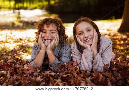 Portrait of happy siblings lying on autumn leaves at park