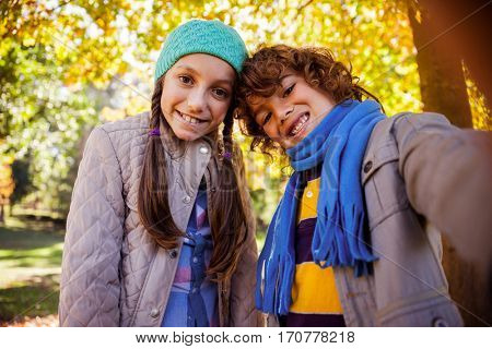 Cheerful siblings taking selfie while standing in park