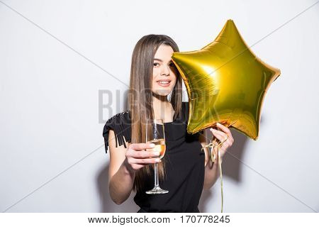 Happy attractive young woman in black dress holding star shaped balloon and drinking champagne over white background