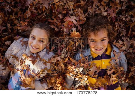 High angle portrait of happy siblings lying on autumn leaves at park